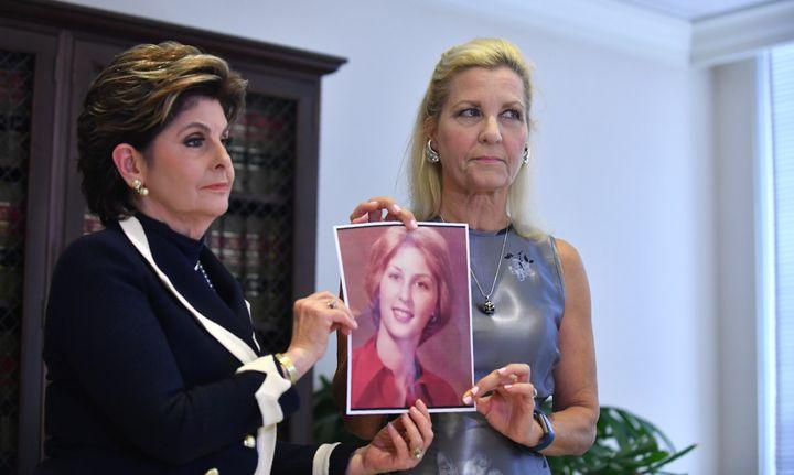 """L'avocate Gloria Allred (à gauche) et une femme se présentant sous le prénom """"Robin"""" (à droite)brandissentune photo d'elle à 16 ans, l'âge auquel elle affirme avoir été agressée sexuellement par Roman Polanski, lors d'une conférence de presse à Los Angeles, le 15 août 2017. (FREDERIC J. BROWN / AFP)"""