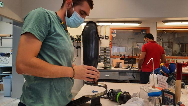 Un employé de Chabloz Orthopédie améliore la prothèse de Jean-Michel, un sexagénaire sportif qui l'utilise pour aller chasser et pêcher. (SIMON CARDONA / RADIO FRANCE)