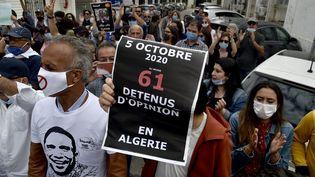 Des Algériens participent à un rassemblement hebdomadaire pour appeler à la libération du journaliste Khaled Drareni à Alger, le 5 octobre 2020.Le journaliste algérien de 40 ans, incarcéré depuis le 29 mars, a été condamné en appel à deux ans de prison. (RYAD KRAMDI / AFP)