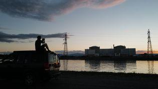 Un homme prend une photo de la centrale nucléaire de Fessenheim (Haut-Rhin), le 29 juin 2020, jour de l'arrêt définitif de la centrale. (SEBASTIEN BOZON / AFP)