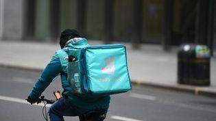 Un livreur employé par Deliveroo à Londres. La société va entrer en bourse mercredi 30 mars. (DANIEL LEAL-OLIVAS / AFP)
