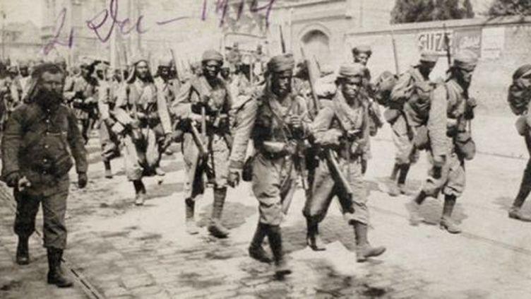 Carte postale montrant des tirailleurs maghrébins marchant dans les rues d'Amiens en 1914 (AFP - STR - Historial de Péronne)