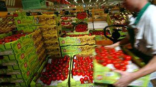 Un magasinier range des caisses de tomates dans une grande surface de Rots (Calvados), le 17 août 2004. (MYCHELE DANIAU / AFP)