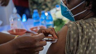 Un médecin ougandais reçoit une première dose du vaccin contre le Covid-19 d'AstraZeneca, le 10 mars 2021. (BADRU KATUMBA / AFP)