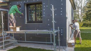 Des plaques d'isolants sont installés sur les murs d'une maison en cours de rénovation, en 2018. (CHASSENET / BSIP / AFP)