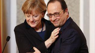 La chancelière allemande Angela Merkel (L) enlace le président français François Hollande lors d'une conférence de presse à l'issue des négociations de paix portant sur le conflit ukrainien à Minsk (Ukraine), le 12 février 2015. (GRIGORY DUKOR / REUTERS)
