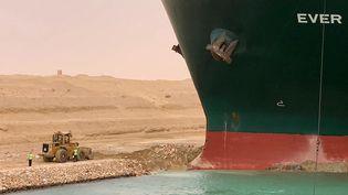 """Unremorqueur est mobilisé pour aspirer le sable sous l'""""Ever Given"""", coincé en travers du Canal de Suez, en Eygpte, le 24 mars 2021. (SUEZ CANAL / AFP)"""