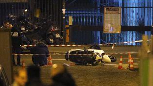 Des enquêteurs autour du scooter des braqueurs abandonnés dans le 15e arrondissement de Paris, à proximité d'un salon de coiffure, après le braquage de la bijouterie Cartier. (KENZO TRIBOUILLARD / AFP)