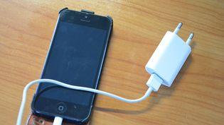 Un smartphone et son chargeur. (JEAN-CHRISTOPHE BOURDILLAT / RADIO FRANCE)
