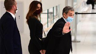 """L'ancien président Nicolas SarkozyetCarla Bruni-Sarkozy, après une audience du procès des """"écoutes"""", le 9 décembre 2020 au palais de justice de Paris. (MARTIN BUREAU / AFP)"""