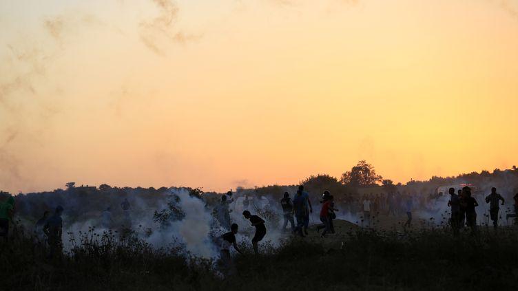 Des Palestiniens affrontent des soldats israéliens tirant des gaz lacrymogènes, le 15 octobre 2015 dans la bande de Gaza. (MOHAMMED ABED / AFP)