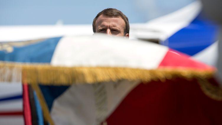 Emmanuel Macron caché par un drapeau français à l'aéroport de Cayenne, en Guyane, le 26 octobre 2017. (RONAN LIETAR / POOL)