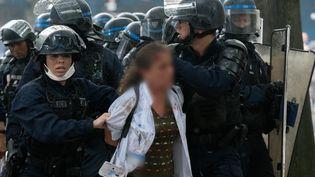 Une infirmière interpellée pendant la manifestation des soignants, à Paris, le 16 juin 2020. (ESTELLE RUIZ / HANS LUCAS / AFP)