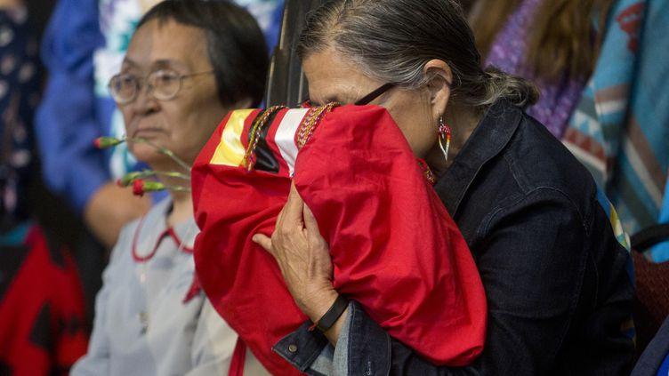 Une femmeâgée embrasse la copie finale de l'enquête nationale sur les femmes et les filles autochtones disparues et assassinées, le 3 juin 2019. (ANDREW MEADE / AFP)