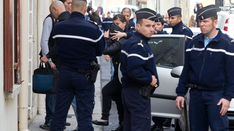La compagne du meurtrier présumé de la petite Océane entourée par des gendarmes, le 10 novembre 2011 à Bellegarde. (PHILIPPE DE POULPIQUET / PHOTOPQR / LE PARISIEN / MAXPPP)