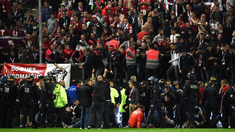 Des supporters lillois tombés à terre après l'effondrement d'unebarrière au stade d'Amiens, le 30 septembre 2017. (FRANCOIS LO PRESTI / AFP)