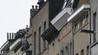 Des forces de sécurité grimpent sur des immeubles à Molenbeek dans la banlieue de Bruxelles, le 16 novembre 2015. (JOHN THYS / AFP)