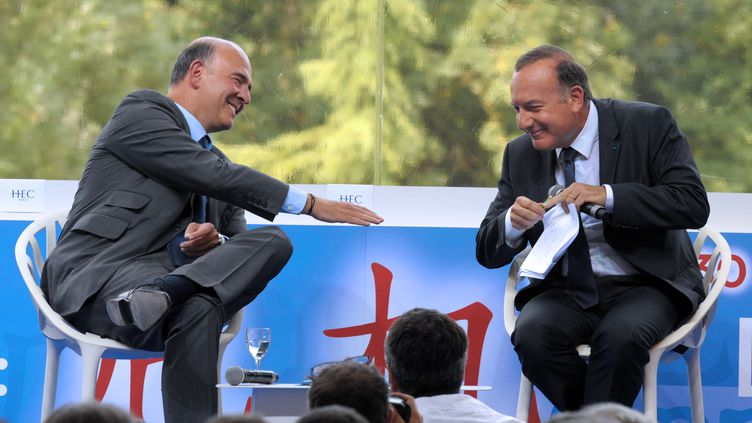 Pierre Moscovici tend la main à Pierre Gattaz, lors du débat réunissant les deux hommes à l'université de Medef, le 29 août 2013, à Jouy-en-Josas (Yvelines). (ERIC PIERMONT / AFP)