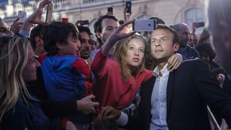 Dans la cour de l'Elysée, ouverte pour la Fête de la musique, le président Emmanuel Macron pose pour un selfie  (Christophe Petit Tesson / pool / AFP)