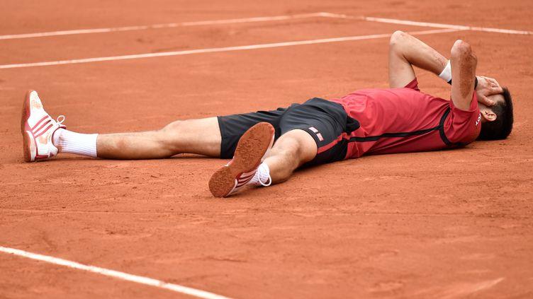 Novak Djokovic au sol après sa victoire en finale de Roland-Garros aux dépens d'Andy Murray (PHILIPPE LOPEZ / AFP)