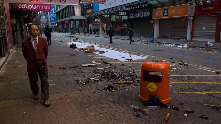 Un passant marche le 9 février 2016 à proximité des débris laissés par une nuit d'émeutes dans le quartier de Mongkok, à Hong Kong. Une centaine de personnes, dont de nombreux policiers, ont été blessées lors de ces incidents survenus aux premières heures, alors que les habitants de l'ancienne colonie britannique fêtaient le Nouvel an chinois. Les troubles ont éclaté lorsque les autorités ont tenté de disperser des vendeurs ambulants non autorisés qui proposaient, entre autres, de la nourriture. Les manifestants, parmi lesquels des membres de la mouvance dite«localiste» qui milite contre l'influence de Pékin à Hong Kong et réclame même parfois l'indépendance de l'archipel, tentaient de prendre la défense des vendeurs, arguant qu'ils participaient à l'atmosphère festive en ce début d'année du singe. (DALE DE LA REY / AFP)