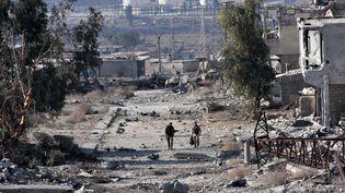 Des membres des forces pro-gouvernementales patrouillent dans un quartier d'Alep-Est (Syrie) repris aux rebelles, le 12 décembre 2016. (GEORGE OURFALIAN / AFP)