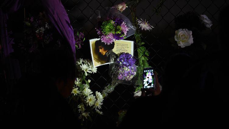 Des photos et des fleurs déposées par des fans en deuil le 21 avril 2016 devant la résidence de Prince à Minneapolis (Eatts-Unis). (MARK RALSTON / AFP)