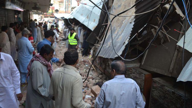 Des Pakistanais sont rassemblés devant des maisons qui se sont effondrées après un séisme de magnitude 7,5, dans la province du Punjab au Pakistan, le 26 octobre 2015. (AZHAR KHAN / ANADOLU AGENCY / AFP)
