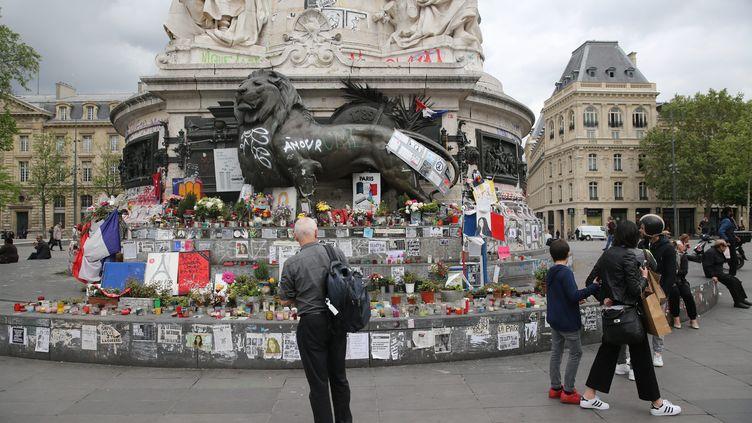 Des passants regardent les hommages et les graffitis laissés sur la statue de la place de la République, à Paris, le 12 mai 2016. (MAXPPP)