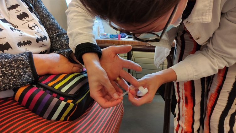 Une infirmière prélève une goutte de sang sur le doigt d'une femme avant qu'elle soit vaccinée contre le Covid, dans un centre de Montreuil, en Seine-Saint-Denis. Cette goutte est ensuite déposée sur un test sérologique rapide pour savoir sicette femme a déjà été contaminée, et donc n'a besoin que d'une dose. (PAOLA GUZZO / RADIO FRANCE)
