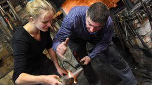 Une jeune apprentie allemande travaille sur une forge. (AFP)