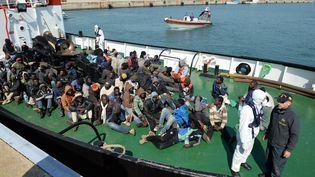 Des migrants rescapés en Méditerranée débarquent le 15 avril 2015 d'un tanker qui les a secourus, sur le port italien deCoriglianoenCalabre. (ALFONSO DI VINCENZO / AFP)