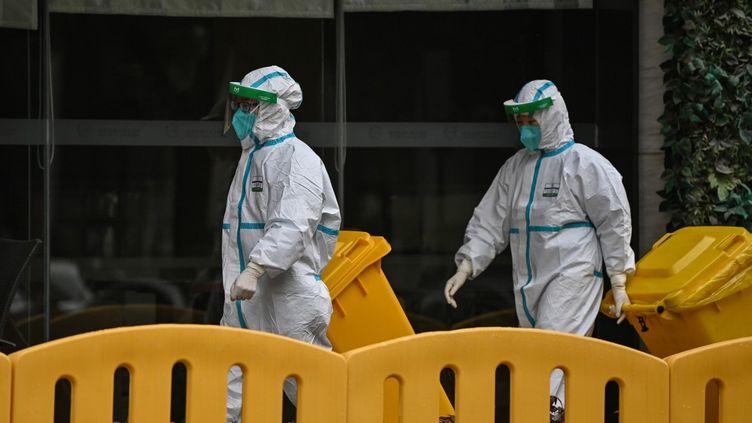 Des travailleurs vêtus de combinaisons de protection, devant l'hôtel dans lequel les enquêteurs de l'OMS se trouvaient en quarantaine jusqu'au 28 janvier 2021. (HECTOR RETAMAL / AFP)