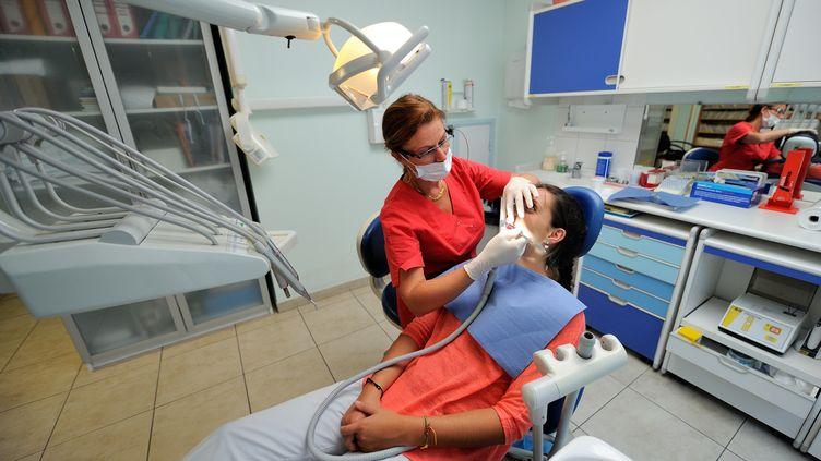 Une dentiste soigne une patiente, le 6 septembre 2013 àBailleul (Nord). (PHILIPPE HUGUEN / AFP)