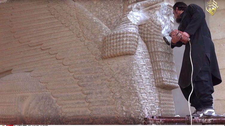 Capture d'écran d'une vidéo de propagande de l'EI montrant un homme détruisant une sculpture assyrienne, au musée de Mossoul, en Irak. La vidéo a été diffusée le 26 février 2015. (AP / SIPA)