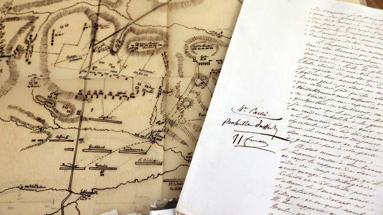 """Le manuscrit relatant la légendaire bataille d'Austerlitz, dicté et annoté par Napoléon durant son exil à Sainte-Hélène, photographié le 25 janvier 2021 avant sa mise en vente par la galerie parisienne """"Arts et autographes"""". Le manuscrit estaccompagné d'un plan de la bataille sur papier calque dessiné par le généralHenri-Gatien Bertrand. (THOMAS COEX / AFP)"""