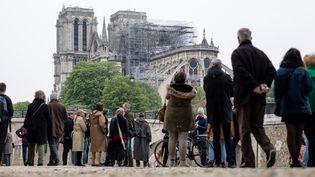 Des badauds observent Notre-Dame de Paris, le 16 avril 2019. (MARCEL KUSCH / DPA / AFP)