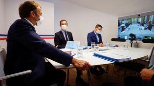 Le président de la République, Emmanuel Macron, avec les ministres Olivier Véran et Alain Griset et le chef d'état-major Jean-Philippe Rolland, au fort de Brégançon (Var) lors d'un Conseil de défense sanitaire en visioconférence, le 11 août 2021. (ERIC GAILLARD / AFP)