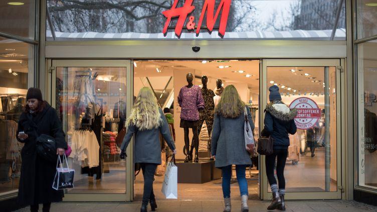 Des passants entrent dans un magasin H&M à Berlin (Allemagne), le 3 janvier 2015. (BERND VON JUTRCZENKA / AFP)