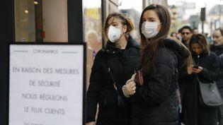 Des clients attendent leur tour devant un supermarché en raison des mesures prises pour lutter contre l'épidémie, le 16 mars 2020 à Paris. (THOMAS SAMSON / AFP)