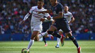 L'attaquant du Paris Saint-Germain, Kylian Mbappé, à la lutte avec le Clermontois Akim Zedadka, samedi 11 septembre 2021. (FRANCK FIFE / AFP)