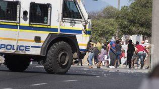 Des habitantsdu township de Mitchells Plain, près du Cap, s'enfuient à l'arrivée d'un véhicule de police pendant des heurts avec les forces de l'ordre le 14 avril 2020. (RODGER BOSCH / AFP)