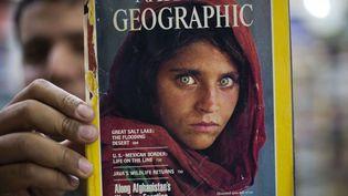 """En 2016, un libraire pakistanais brandit un exemplaire du """"National Geographic""""avec """"l'Afghane aux yeux verts"""" en couverture. (B.K. BANGASH/AP/SIPA / AP)"""