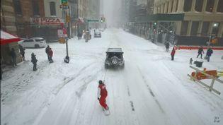 Un New-Yorkais en snowboard se fait tracter par un 4x4, à New York, pendant la tempête Jonas, le 23 janvier 2016. Au moins 19 personnes sont mortes dans ce qui contistitue une des pires tempêtes de neige de l'histoire de la côte Est des Etats-Unis. (CASEY NEISTAT / YOUTUBE)