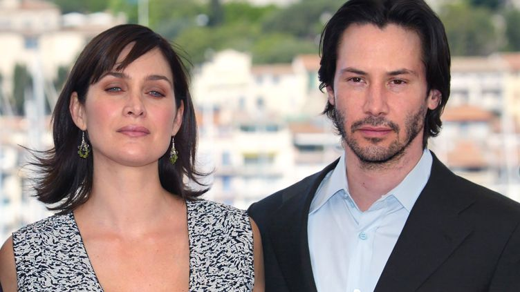 """Keanu Reeves et Carrie-Anne Moss, acteurs principaux de la saga Matrix, à Cannes à l'occasion de la sortie de """"Matrix Reloaded"""", le 15 mai 2003. (FRANCOIS GUILLOT / AFP)"""