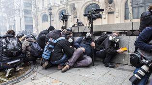 """Des journalistes s'abritentsur les Champs-Elysées, le 8 décembre 2018, à Paris, pendant la manifestation des """"gilets jaunes"""". (YANN CASTANIER / HANS LUCAS / AFP)"""
