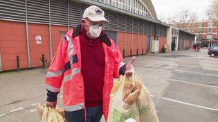 Un membre du Seamen's club du Havre apporte de la nourriture aux marins d'un bateau à quai sur le port. (FRANCEINFO)