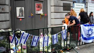 Des personnes déposent des gerbes devant l'entrée du Musée juif, le 25 mai 2014 à Bruxelles. (DURSUN AYDEMIR / ANADOLU AGENCY / AFP)