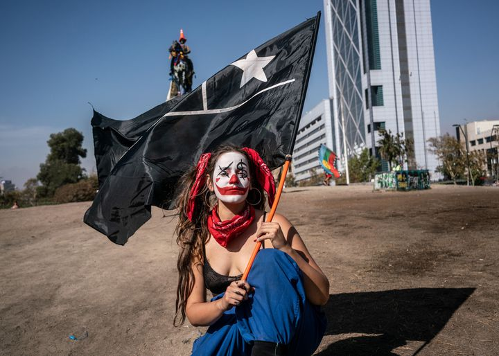 VIVIR PARA CONTARLO - Santiago de Chile. A clown-clad protester holds a totally black flag of Chile in Plaza de la Dignidad (former Plaza Italia) in memory of the street artist girl arrested by the Chilean police and found a few days later hanged in a park in the capital after being repeatedly raped. The black flag is a sign of mourning for the violence perpetrated by law enforcement and the state during the days of repression. (KARL MANCINI)