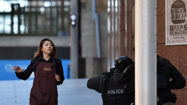 Une personne retenue en otage dans un café de Sydney (Australie) parvient à s'enfuir, lundi 15 décembre 2014. (SAEED KHAN / AFP)